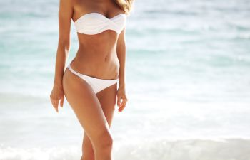 Woman Strolling on the Beach After Liposuction Treatment inAtlanta GA